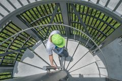 The boy and circular stairs. The boy in a green cap walk downward on circular stairs royalty free stock photography