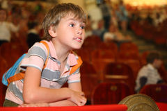 Boy in circus leans on rail looking into distance. Little boy in circus leans on red rail looking into the distance and waiting for performance start stock photography