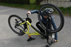 Boy checks his bike. Teenage boy checking his bike Stock Photos
