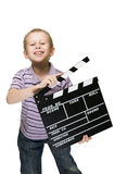 Boy with clapperboard grinning Royalty Free Stock Photo