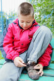Boy clasping shoes Royalty Free Stock Photo