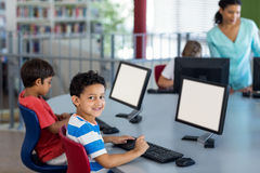 Boy with classmates and teacher during computer class. Portrait of smiling boy with classmates and teacher during computer class Royalty Free Stock Images
