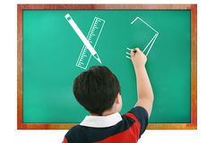 Boy in classroom thinking and writing Stock Images