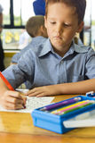 Boy in classroom working Royalty Free Stock Photo