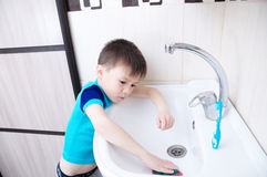 Boy cleaning in bathroom wash sink, child doing up housework helping mother with sanitary cleanness of home. Training kid for housekeeping royalty free stock photo