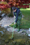 Boy cleaning garden pond. Boy in green waterproof  dungarees cleaning a garden pond in autumn Stock Photo