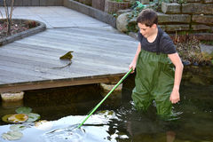 Boy cleaning garden pond Stock Photos