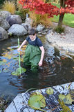 Boy cleaning garden pond Royalty Free Stock Images