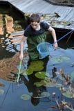 Boy cleaning garden pond Stock Photo