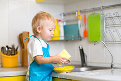 Boy cleaning the kitchen after making dinner Royalty Free Stock Photo