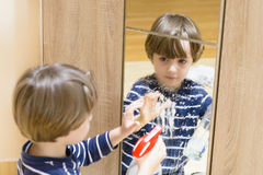 Boy Cleaning the Mirror Royalty Free Stock Images
