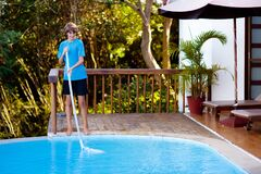 Boy cleaning swimming pool. Maintenance, service