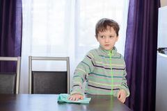 Boy cleaning table in kitchen Royalty Free Stock Images