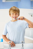 Boy cleaning teeth in bathroom Stock Photography