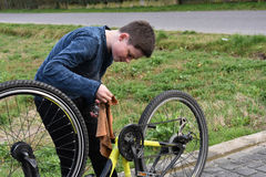 Boy cleans bicycle Stock Image