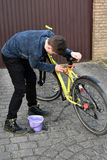 Boy cleans bicycle Royalty Free Stock Photography
