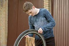 Boy cleans bike Royalty Free Stock Image
