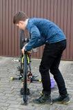 Boy cleans bike Royalty Free Stock Photo