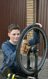 Boy cleans bike Royalty Free Stock Images