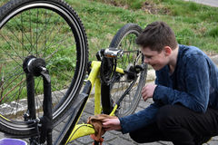 Boy cleans bike. Boy is cleaning his bike Royalty Free Stock Image
