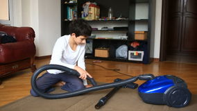 The boy cleans the carpet in the room with a vacuum cleaner stock footage