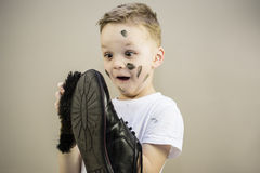 Boy cleans dirty shoes Royalty Free Stock Photo