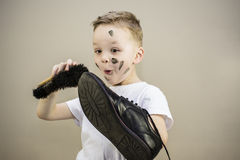 Boy cleans dirty shoes Royalty Free Stock Images