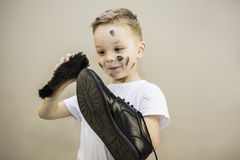 Boy cleans dirty shoes Stock Photo