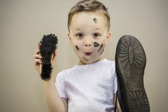 Boy cleans dirty shoes Stock Photos