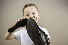 Boy cleans dirty shoes Stock Images