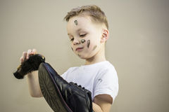 Boy cleans dirty shoes Stock Image