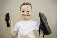 Boy cleans dirty shoes Royalty Free Stock Photos