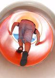 Boy clibming up on a cylindric slide Stock Photo