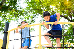 Boy climb on the rope fence. Young asian boy climb on the black rope fence and yellow bar by his hand to exercise at out door playground under the big tree stock photography