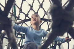 Boy climb rope tunnel. Chinese boy climb rope tunnel on playground royalty free stock photo