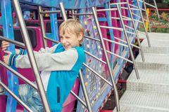 Boy climbed up on the extreme carousel Royalty Free Stock Images