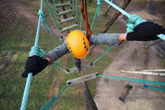 Boy climber walks on the rope bridge Stock Photography