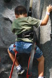 Boy climbing. This young boy is working hard to reach the top of this rock climbing cliff Royalty Free Stock Photos