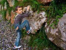 Boy climbing. Cute boy climbing a wall of stones Royalty Free Stock Photos