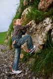 Boy climbing. Cute boy climbing a wall of stones Royalty Free Stock Photo