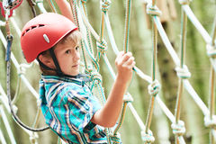 Boy at climbing activity in high wire forest park. Adventure rope way and extreme activity. Scout boy climbing on high wire park in the forest Stock Photos
