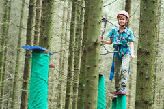 Boy at climbing activity in high wire forest park. Adventure rope way and extreme activity. Scout boy climbing on high wire park in the forest Royalty Free Stock Image