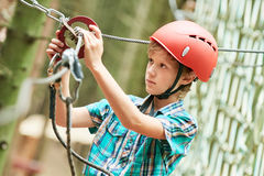 Boy at climbing activity in high wire forest park. Adventure rope way and extreme activity. Scout boy climbing on high wire park in the forest Stock Photography