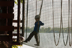 Boy climbing in adventure park , rope park Stock Photos