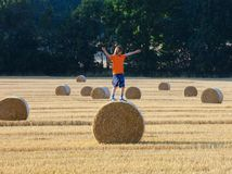 Boy Climbing a Bale of Hay on a Field Royalty Free Stock Photos