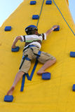 Boy climbing a climbing wall. Royalty Free Stock Image