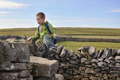 Boy climbing dry-wall in English countryside. English countryside landscape with a boy climbing over drystone wall, Yorkshire Dales, England, United Kingdom Stock Images