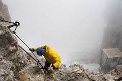 Boy climbing Germany highest mountain Zuhspitze in foggy weather Royalty Free Stock Photography