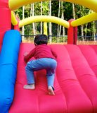 Boy climbing on inflatable castle Royalty Free Stock Image