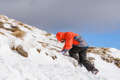 Boy climbing on mountain in wintertime. Cute little kid boy in c. Olorful winter clothes climbing mountain covered with snow Royalty Free Stock Photos